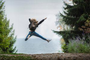 Frau mit rucksack springt
